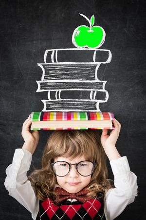 Slimme jongen in de bibliotheek. Gelukkig kind tegen schoolbord. Onderwijs concept