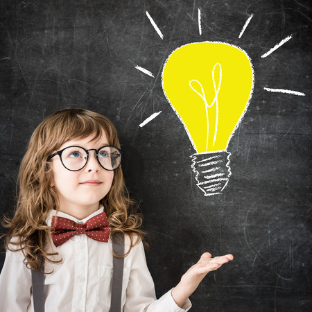 blackboard background: Smart kid in class. Happy child against blackboard. Drawing light bulb. Business idea concept