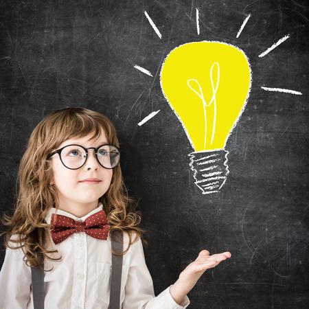 smart kid: Smart kid in class. Happy child against blackboard. Drawing light bulb. Business idea concept