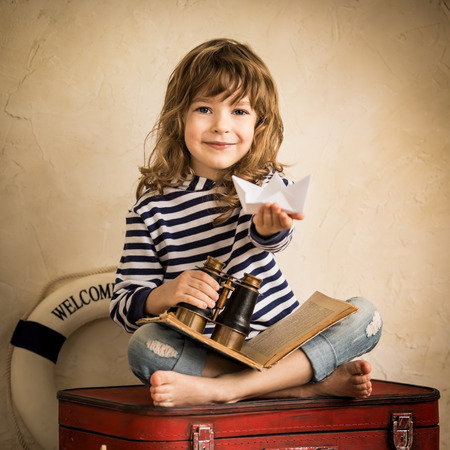 Happy kid playing with paper sailing boat indoors. Travel and adventure concept photo