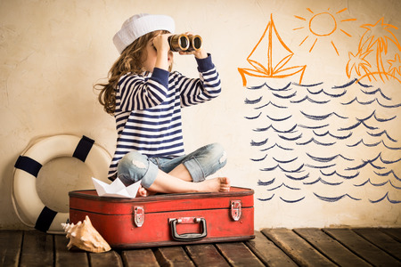 Happy kid playing with toy sailing boat indoors. Travel and adventure concept Imagens