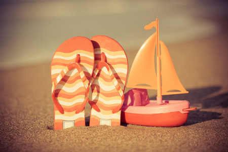 Toy boat and flip flops at the beach. Summer vacation concept