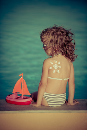 Sunscreen lotion sun drawing on children back. Summer vacation concept photo