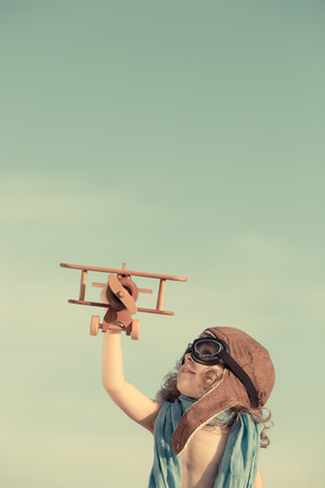 Happy child playing with toy airplane against summer sky background. Travel and adventure concept. Retro toned photo