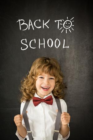 Happy child against blackboard. photo