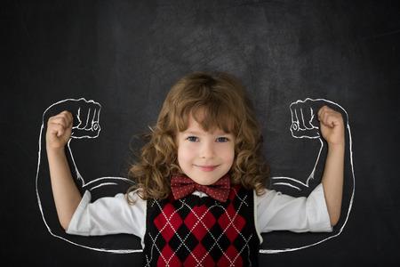 Gelukkig kind tegen schoolbord.