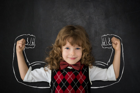 strong: Happy child against blackboard.
