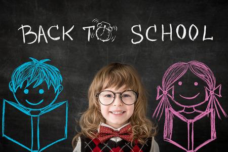 Happy children against blackboard.  photo