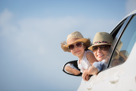 happy family concept: Happy woman and child in car against blue sky background.