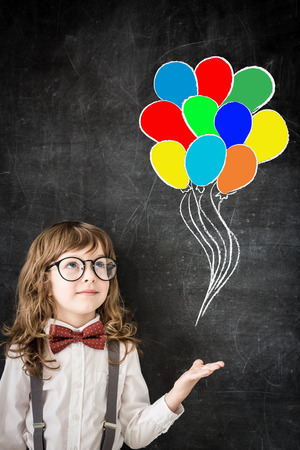 Happy child against blackboard with drawing colored balloons.  photo