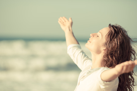 manos levantadas al cielo: Hermosa mujer disfrutando de la vida en la playa.