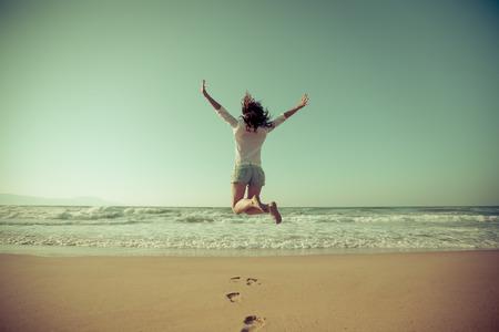 幸せな女ビーチでジャンプします。