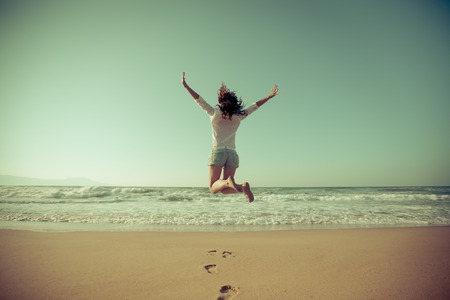 Happy woman jumping at the beach.