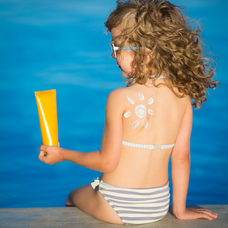 sunscreen: Sunscreen lotion sun drawing on children back. Summer vacation concept