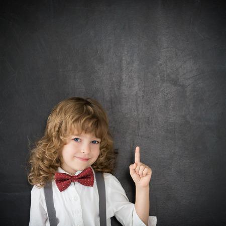 Slimme jongen in de klas. Gelukkig kind tegen schoolbord. Onderwijs concept