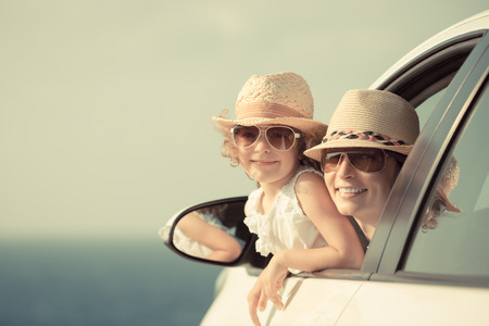 Happy woman and child in car against sea and sky background. Summer vacation concept. Toned image