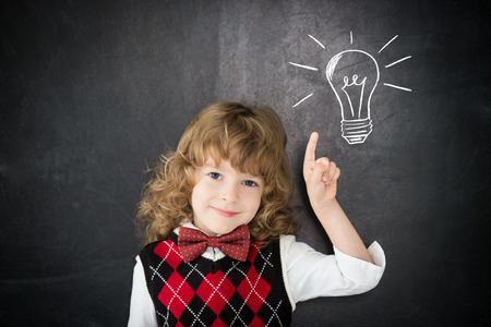 Smart kid in class. Happy child against blackboard. Drawing light bulb. Idea concept photo