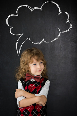 Smart kid in class. Happy child against blackboard. Drawing speech bubble cloud. Copy space for your text photo