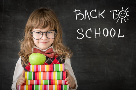 Smart kid in class. Happy child against blackboard. Education concept Stock Photo - 28647030