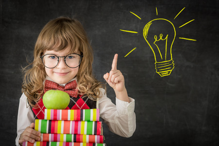 Smart kid in class. Happy child against blackboard. Drawing light bulb idea. Education concept Фото со стока