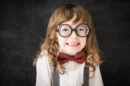 mischief: Curly-headed mischief nerd kid in class. Funny geek against blackboard. Education concept