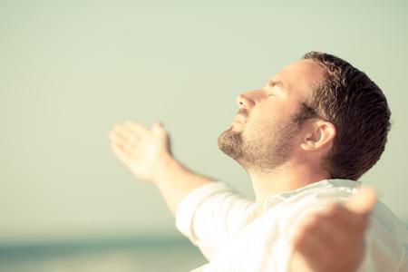 happy holidays: Knappe man genieten van het leven op het strand. Zomer vakantie en vrijheid concept