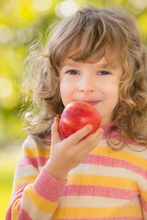 Happy child eating red apple outdoors in autumn park Stock Photo - 30826125