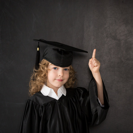 Smart kid in class against blackboard Stock Photo