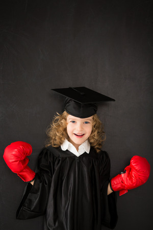Smart kid in class wearing boxing gloves against blackboard Stock Photo - 30826160