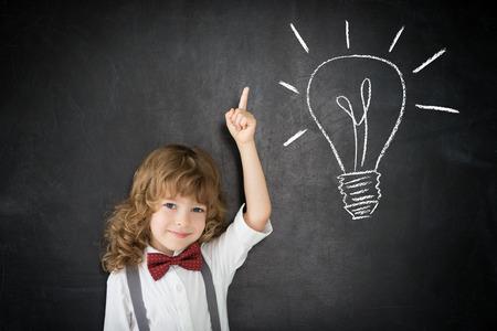Happy child against blackboard light bulb drawing