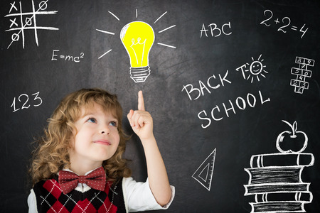 Smart kid in class against blackboard Stock Photo