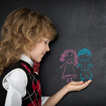 Happy child against blackboard with kids drawing in hand photo