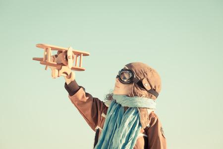 Feliz niño jugando con avión de juguete de madera contra el fondo del cielo de otoño. Retro tonificado
