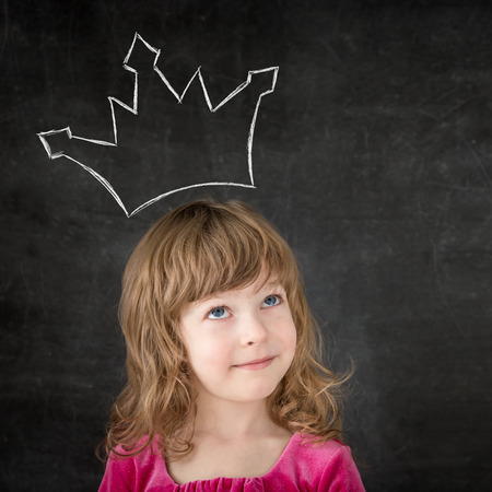 Funny child against blackboard. Smiling girl with drawing crown Banque d'images