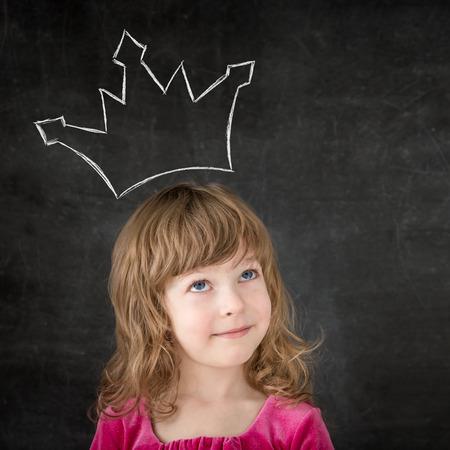 corona reina: Niño divertido contra la pizarra. Muchacha sonriente con la corona de dibujo