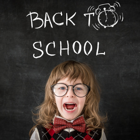 Smart kid in class. Happy child against blackboard. Education concept photo