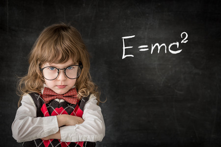education concept: Smart kid in class. Happy child against blackboard. Education concept Stock Photo