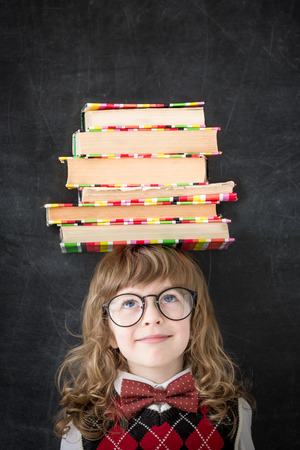 education concept: Smart kid in library. Happy child against blackboard. Education concept