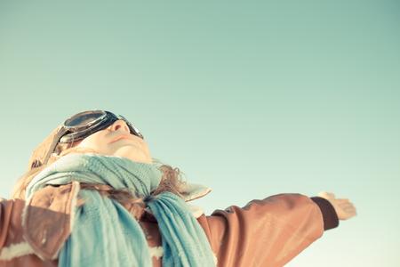 pilotos aviadores: Feliz ni�o jugando con avi�n de juguete de madera contra el fondo del cielo de oto�o. Retro tonificado