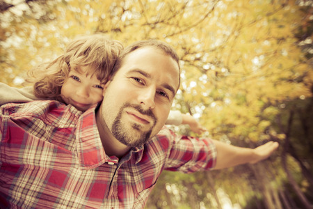 Happy family having fun outdoors in autumn park against yellow blurred leaves background photo