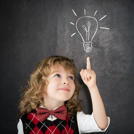 Smart kid in class. Happy child against blackboard. Drawing light bulb. Idea concept