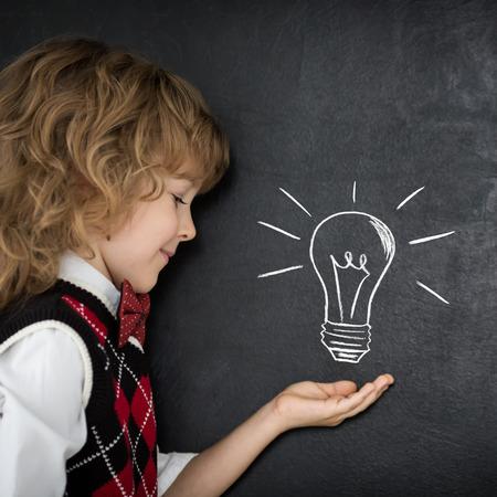Smart kid in class. Happy child against blackboard. Idea concept photo