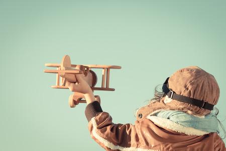 piloto de avion: Feliz niño jugando con avión de juguete de madera contra el fondo del cielo de otoño. Retro tonificado