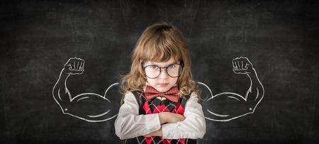 Sterke kind in de klas. Grappig kind tegen schoolbord. Onderwijs concept