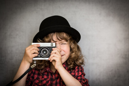 Hipster kid taking a photo using vintage film camera photo