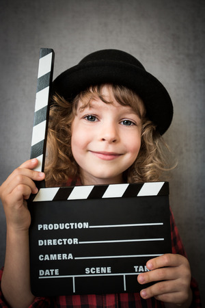 Happy child holding clapper board against grunge wall background. Cinema concept photo