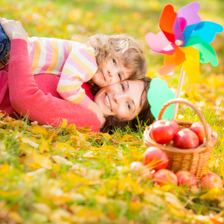 Happy family playing outdoors in autumn park photo