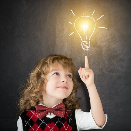 クラスでの賢い子供。黒板に対して幸せな子供。図面の電球。考え概念