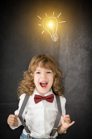 Laughing kid in class. Happy child against blackboard. Education concept photo