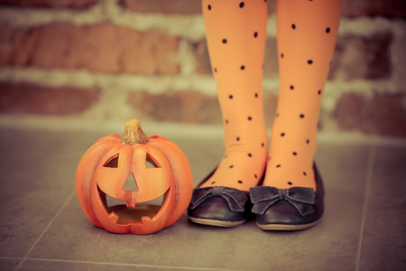 Funny child dressed witch costume holding pumpkin. Halloween holidays concept 스톡 콘텐츠